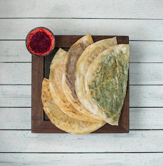 Caucasian kutab in lavash with paprika on a wooden board.