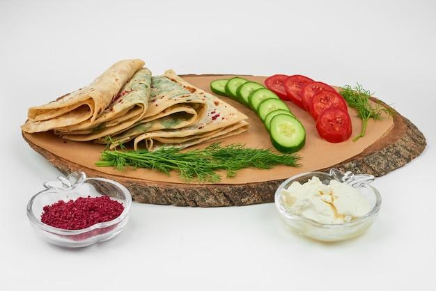 Kutab caucasico con spezie e verdure su una tavola di legno sul bianco.
