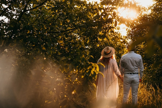 Caucasian lady dressed in a white dress is walking with her lover in a garden full of trees wearing hats in a summer evening