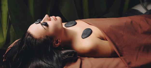 수건으로 덮여 거짓말 스파 살롱에서 돌으로 전신 마사지 세션을 갖는 백인 아가씨