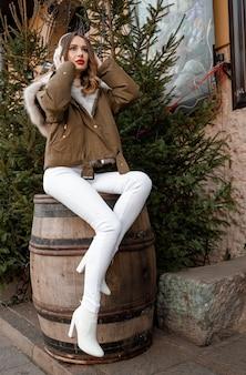 니트 스웨터와 푹신한 헤드폰에 백인 아가씨. 젊은 아름 다운 행복 한 웃는 여자의 야외 초상화 장식 된 크리스마스 트리 근처 모피 코트를 입고있다. 폴란드