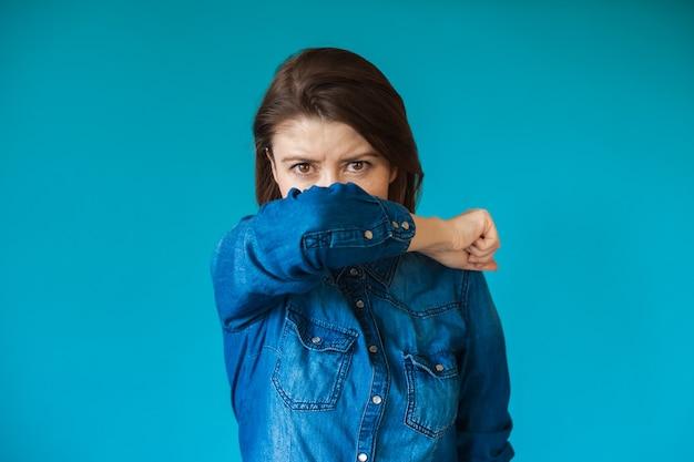 青い壁にポーズをとっている白人女性は、いくつかの呼吸器系の問題を抱えています