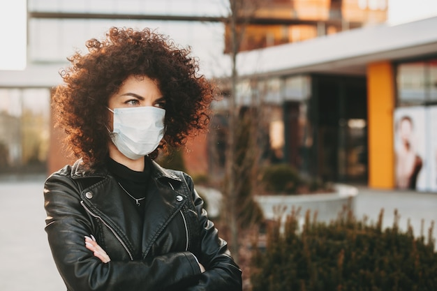 Caucasian lady with curly hair is posing with crossed hands while wearing an anti virus mask