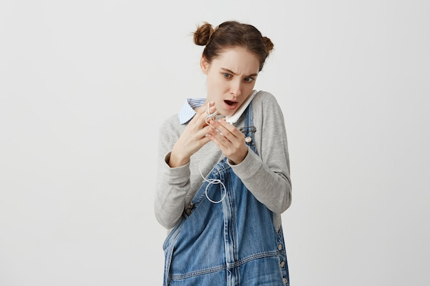 Кавказская дама с модной прической, держа смартфон с плеча, распутывая наушники. девушка, имеющие небольшие проблемы после ношения гаджет в кармане. ситуация и решение