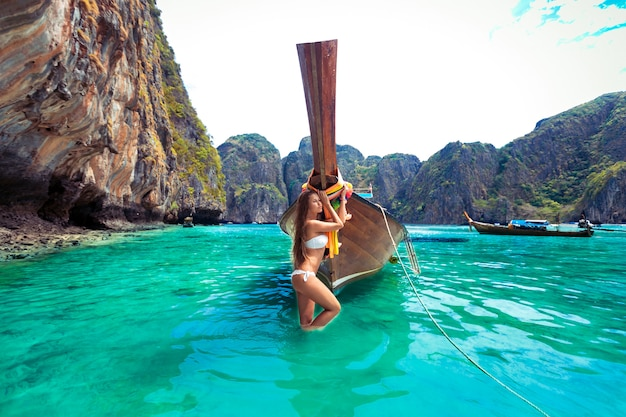 Caucasian lady with slim body relaxing and standing near  long tail boat at beach, phi phi island near phuket in thailand. beautiful turquoise water and big rocks landscape