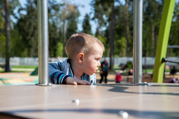 Caucasian little boy climbs the slide on his own to slide down in the playground outdoors on a sunny day.