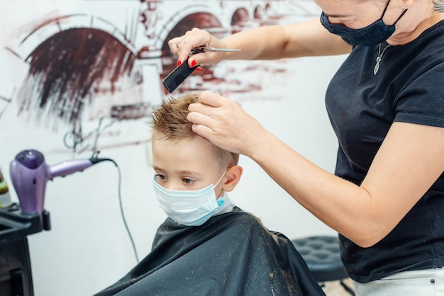 Caucasian little boy getting hair cut at the barbershop wearing protective mask