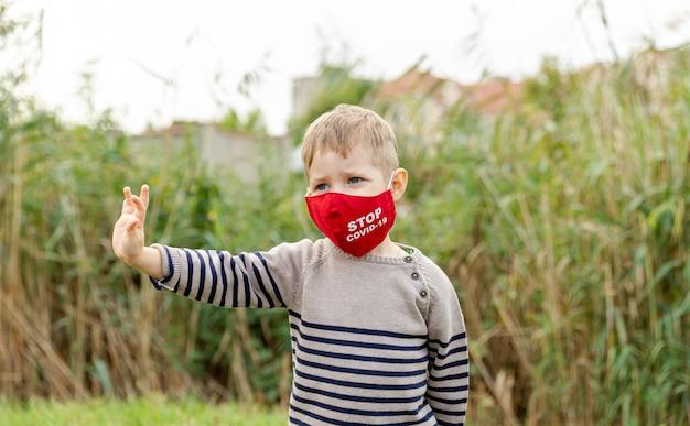보호 마스크에 백인 어린 소년입니다. 귀여운 소년은 마스크를 쓰고 질병 바이러스의 확산을 보호합니다. 코로나 바이러스 감염증 -19 : 코로나 19. 대유행 중 코로나 바이러스 예방. 보건 의료. 보호