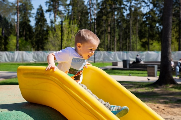 Caucasian little boy slides down the hill at the playground outdoors on a sunny day.