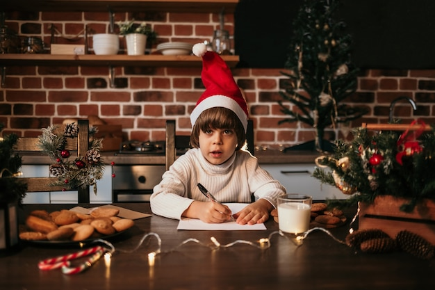A caucasian little boy in a white knitted sweater and a red new year's hat is sitting on the kitchen table and writing a new year's message