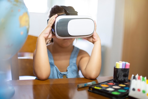 Кавказская маленькая девочка на своем столе в очках vr. концепция новых средств обучения.