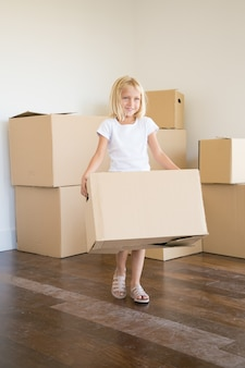 Caucasian little girl carrying cardboard box during removal