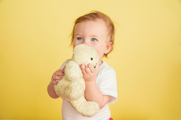 Caucasian little girl, children isolated on yellow studio background. portrait of cute and adorable kid, baby playing with teddy bear.