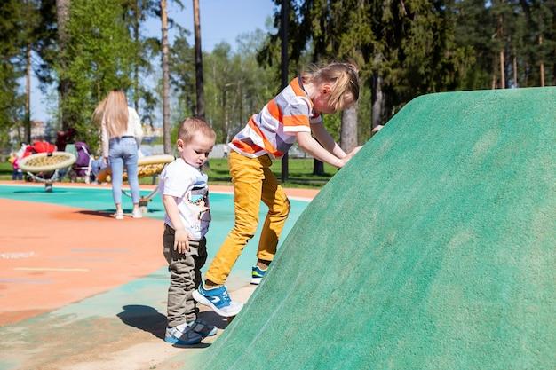 화창한 날 야외 놀이터에서 어린이 암벽을 등반하는 백인 소녀.