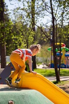 Caucasian little girl climbs the slide to slide down in the playground outdoors on a sunny day.