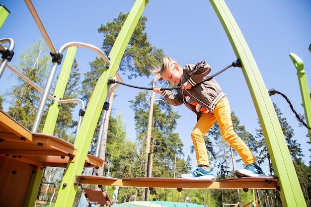 Caucasian little girl climbs the suspension bridge on the obstacle course at the playground outdoors on a sunny day.