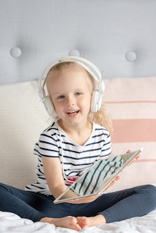 Caucasian little girl in headphone watching tablet in bed, home interior, modern device technologies scandinavian style