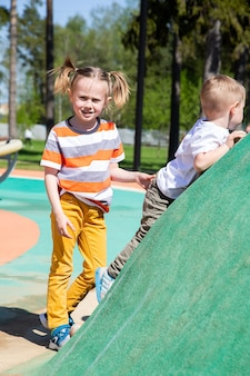 Caucasian little girl helps her small brother climb the children's climbing wall at the playground outdoors on a sunny day.
