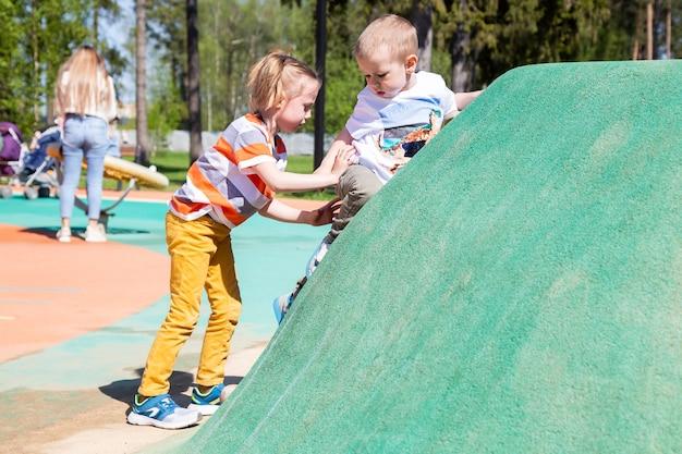 백인 어린 소녀는 어린 동생이 놀이터에서 어린이 암벽을 오르는 것을 돕습니다