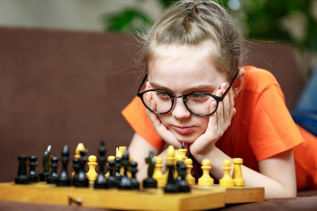 検疫中に自宅でチェスをするチェスゲームを考えている眼鏡をかけた白人の少女。幼児期の発達。