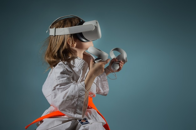 Vr ヘッドセットでビデオ ゲームをする空手の制服を着た白人の少女