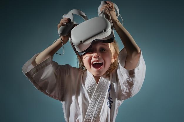 Кавказская маленькая девочка в униформе карате играет в видеоигры с гарнитурой vr