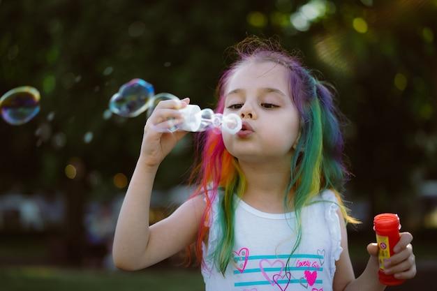 백인 어린 소녀가 선택적 초점을 가진 공원 이미지에서 비누 방울을 불고 있다