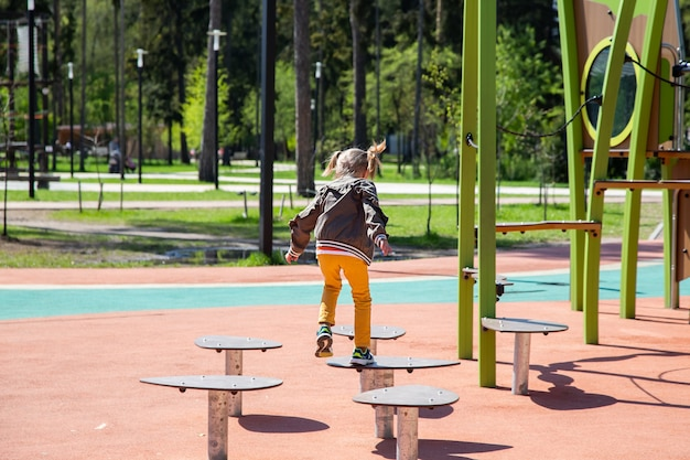 Caucasian little girl jumping on the simulator on the obstacle course in the playground outdoors on a sunny day.