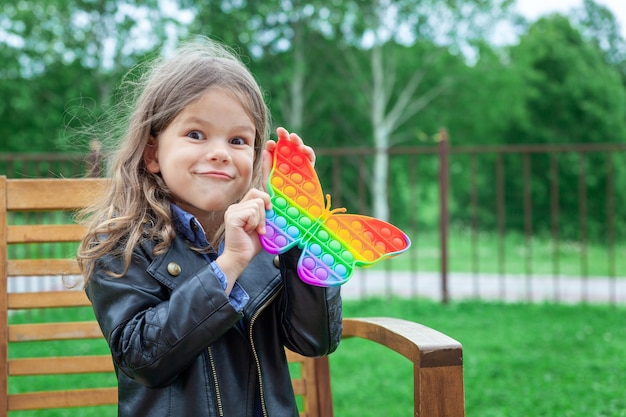 Caucasian little girl playing with pop it silicone trendy rainbow colow toy