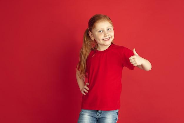 붉은 벽에 고립 된 백인 어린 소녀 초상화