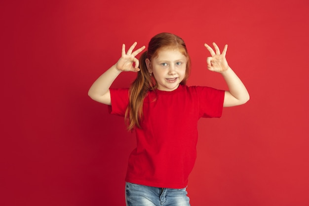 赤い壁に分離された白人の少女の肖像画