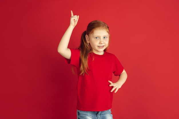 Caucasian little girl portrait isolated on red wall