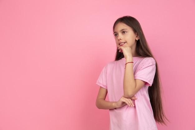 Caucasian little girl portrait on pink wall
