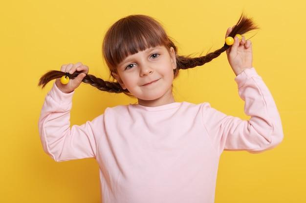 Кавказская маленькая девочка тянет себя за косички, глядя прямо с милой очаровательной улыбкой, ребенок в повседневной бледно-розовой рубашке изолирован на желтой стене.