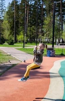 Кавказская маленькая девочка катается на тарзанке на детской площадке и улыбается на открытом воздухе в солнечный день.