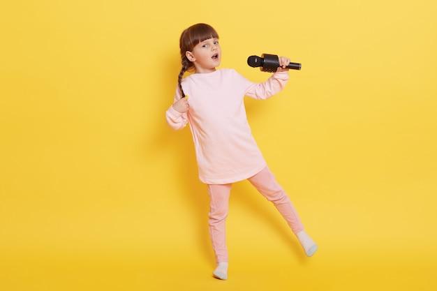마이크와 춤을 추는 백인 어린 소녀, 귀여운 작은 예술가가 노란색 벽 위에 절연되어 캐주얼 의류를 입고 매력적인 가수가 누군가를 위해 노래합니다.