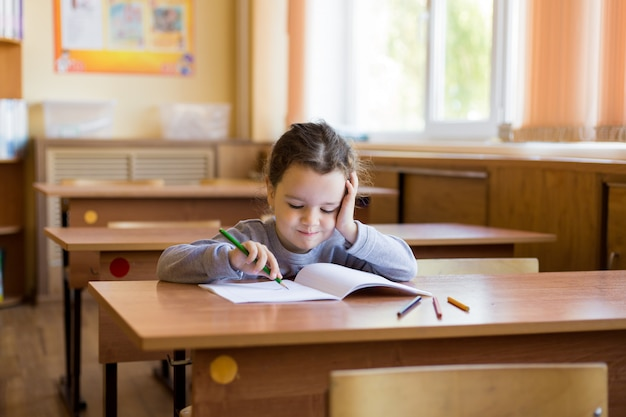Caucasian little girl sitting at desk in class room and begins to carefully draw in a pure notebook.