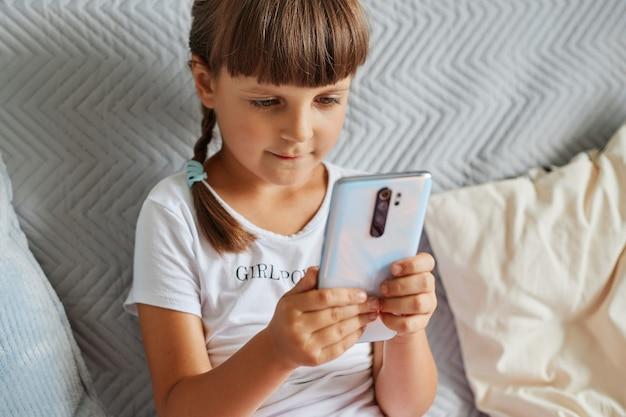 Кавказская маленькая девочка сидит на диване с мобильным телефоном в руках, темноволосый ребенок женского пола играет в игры на смартфоне, одетый в белую футболку повседневного стиля.