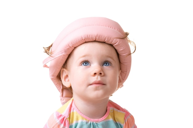 Caucasian little girl wearing a pink  helmet looking up, baby isolated over white background