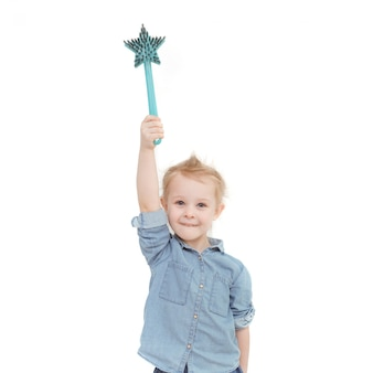 Caucasian little girl with blond hair in a denim shirt holding a brush