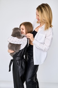Caucasian little girl with her mother holds cat in the arms isolated on white