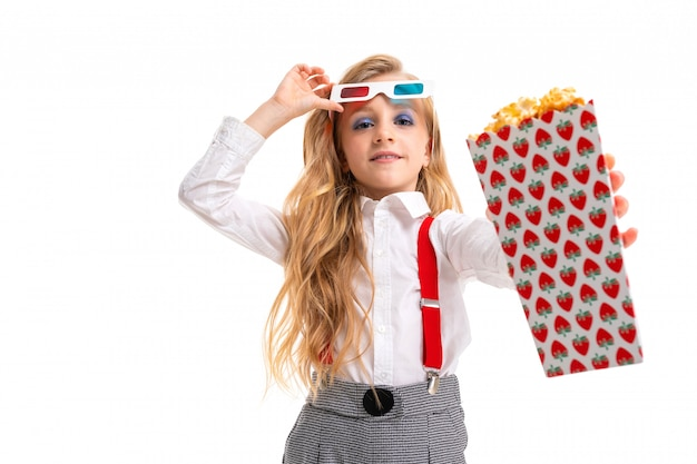 Caucasian little girl with makeup and long blonde hair with pop-corn and 3d glasses