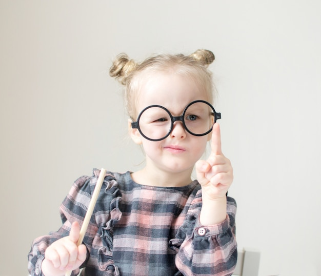 Caucasian little girl with round glasses. little teacher. funny glasses humor. retro style