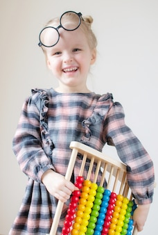 Caucasian little girl with round glasses.
