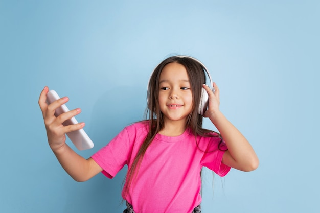 Caucasian little girls portrait on blue studio wall