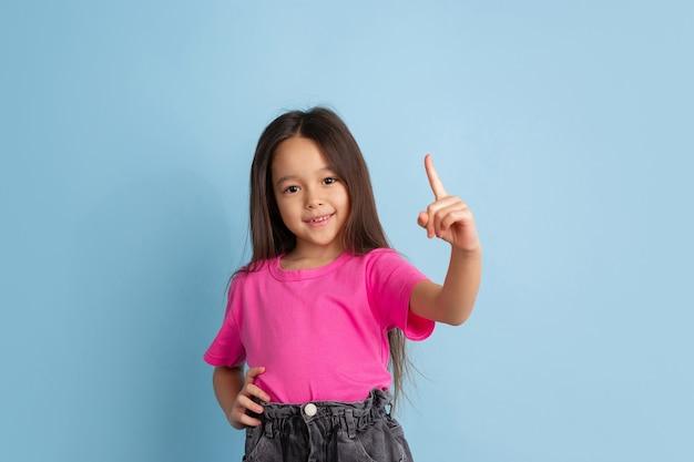 Caucasian little girls portrait on blue  wall