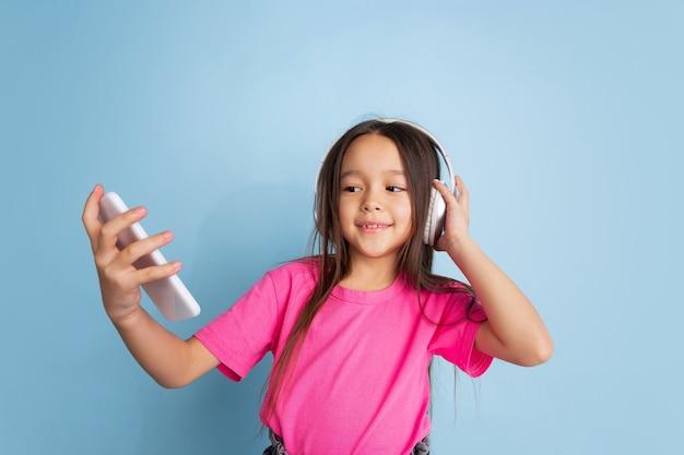 青いスタジオの壁に白人の小さな女の子の肖像画