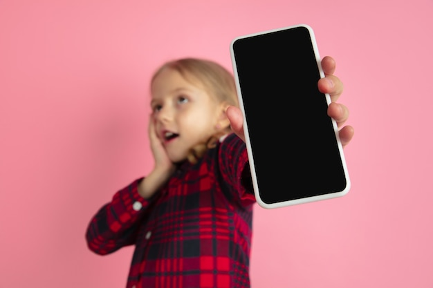 ピンクのスタジオの壁に白人の小さな女の子の肖像画