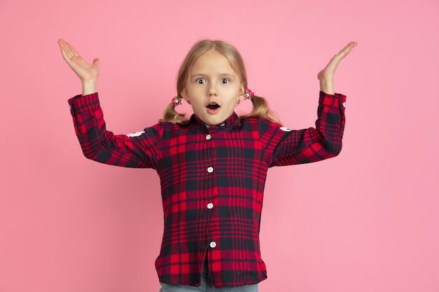 Портрет кавказской маленькой девочки на розовой стене