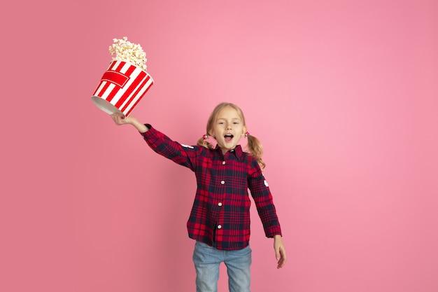 Ritratto di bambine caucasiche sul concetto di cinema a parete rosa